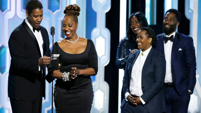 Denzel Washington receiving the Cecil B. DeMille Award on stage with his wife and 3 of his 4 kids